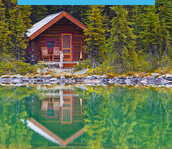 Photo of a small cabin surrounded by pine trees and next to a still lake