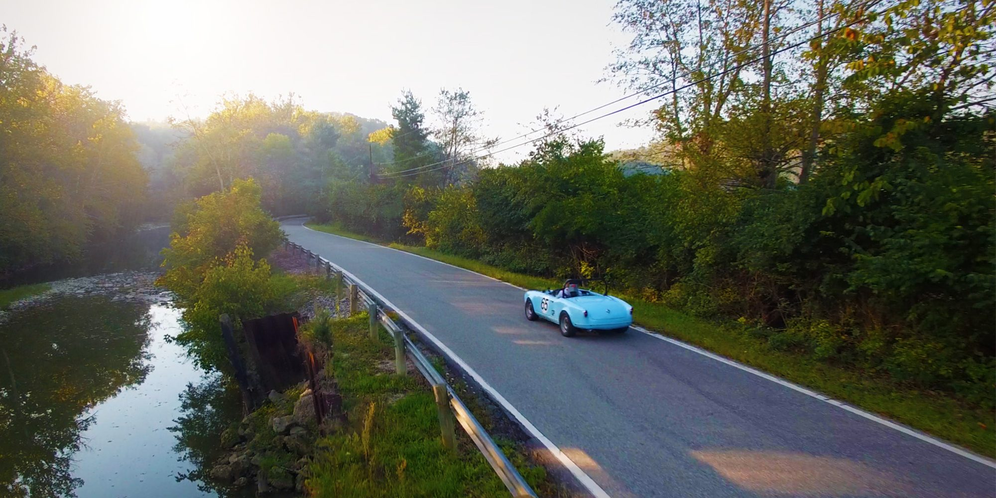 A blue car drives on a road next to a river