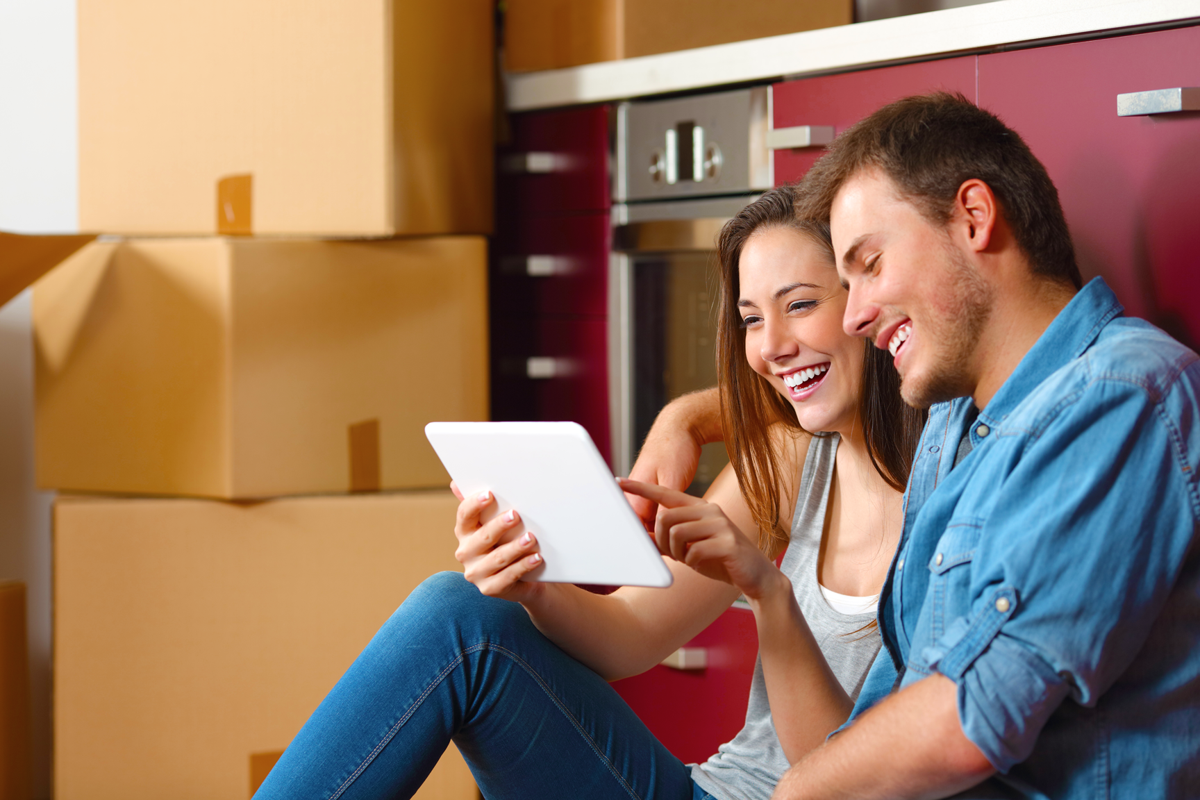 A man and a woman who are surrounded by cardboard boxes smile at a tablet