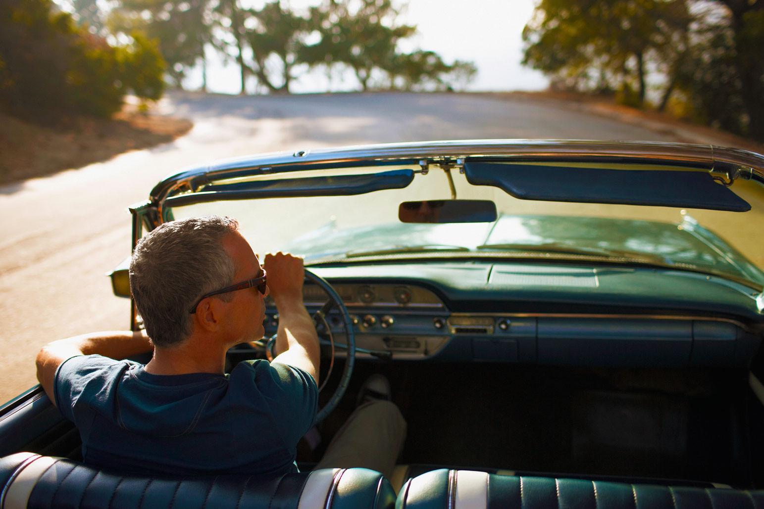 Man with grey hair driving convertible car down a sunny road