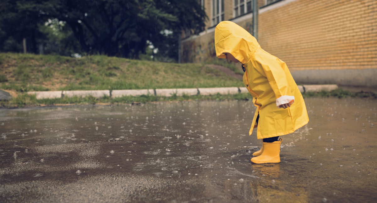 Child in yellow raincoat looks at puddle