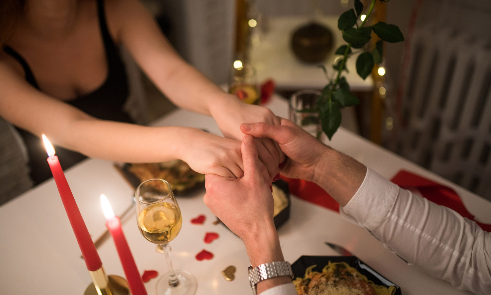 A couple hold hands over a candle-lit dinner