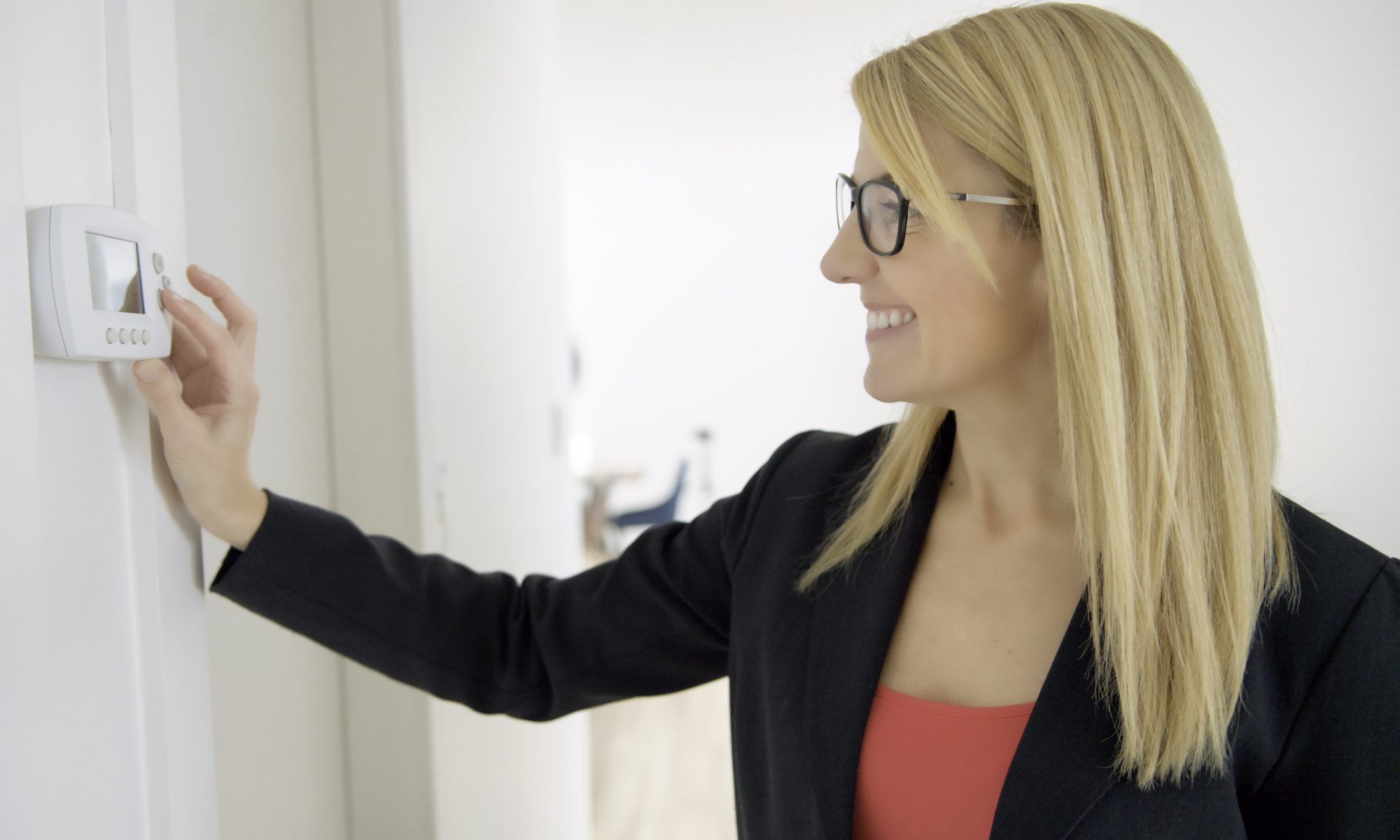 Blonde woman adjusts a thermostat