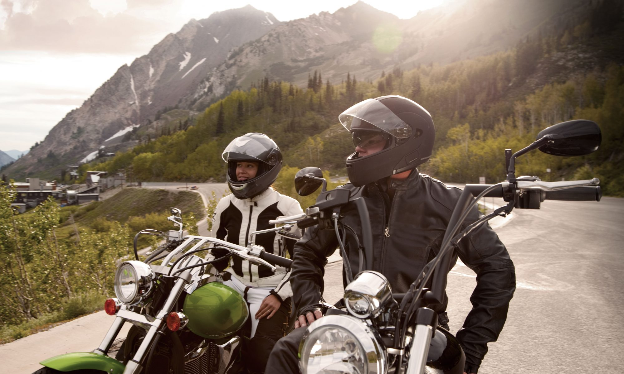 A man and a woman on separate motocycles are stopped on a mountains road