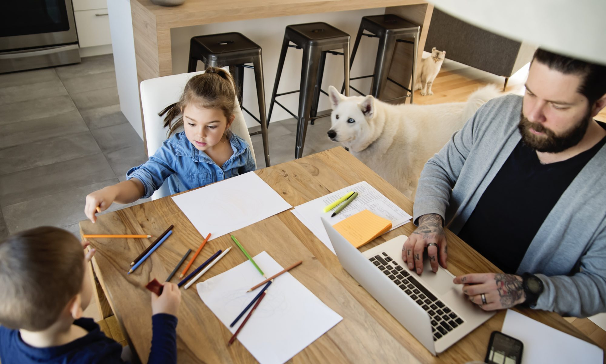 A father works from his kitchen table with two small children who color nearby