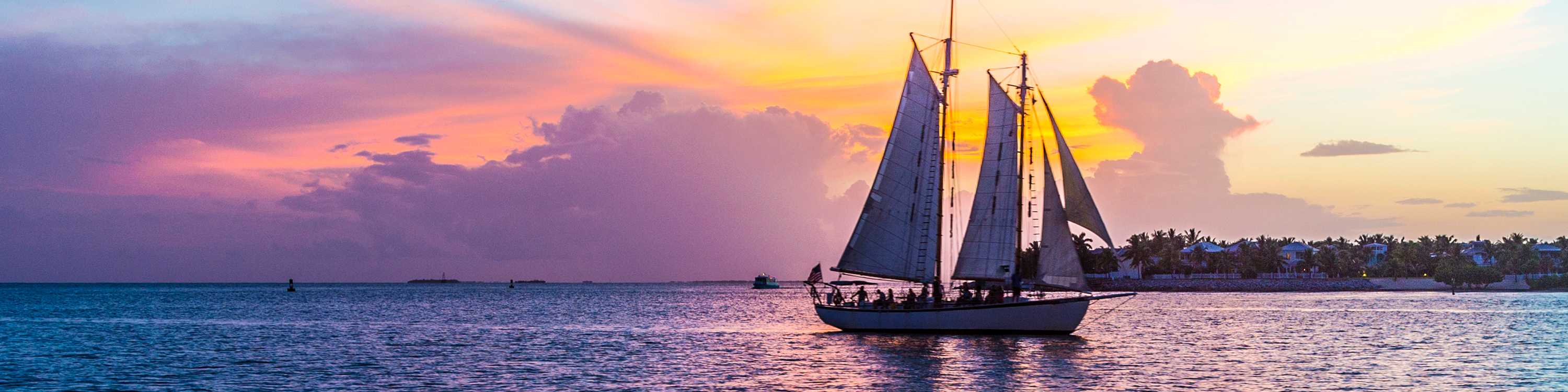 Photo of a sailboat on calm water in front of a sunset